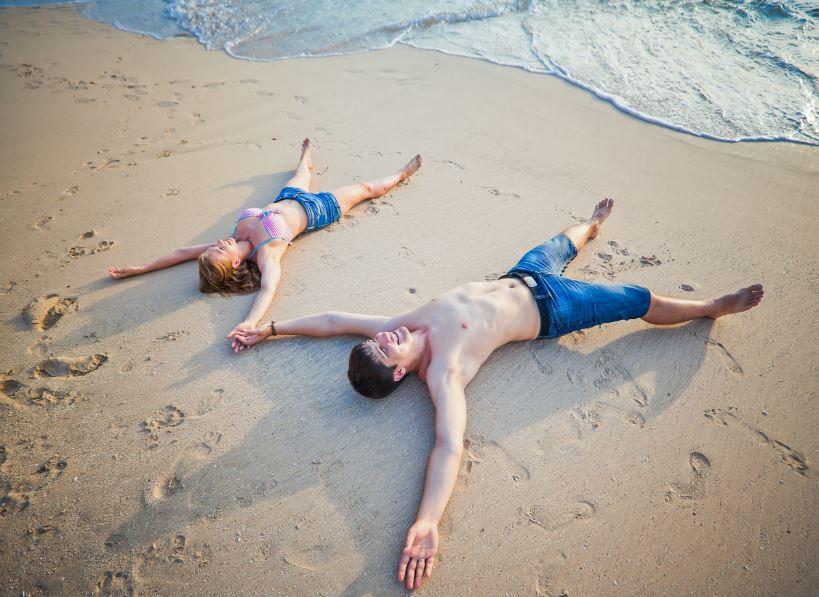 Mladý pár na písečné pláži u moře